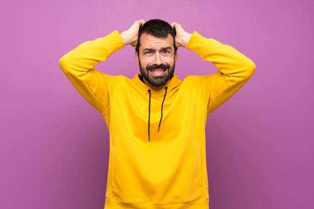 Handsome man with yellow sweatshirt frustrated and takes hands on head