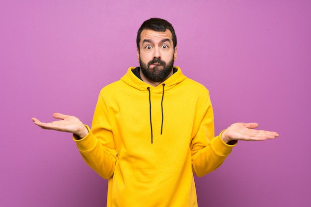 Handsome man with yellow sweatshirt having doubts while raising hands