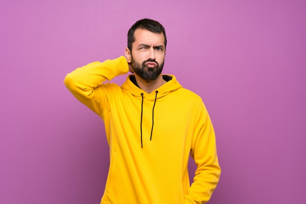 Handsome man with on yellow sweatshirt having doubts