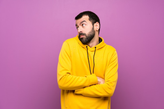 Handsome man with yellow sweatshirt making doubts gesture while lifting the shoulders