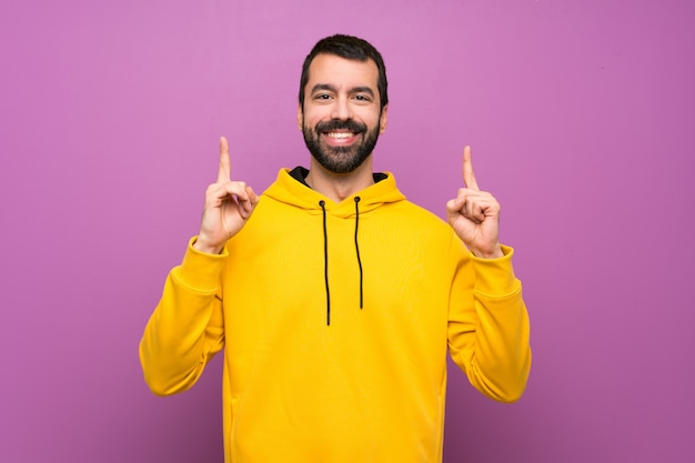 Handsome man with yellow sweatshirt pointing up a great idea
