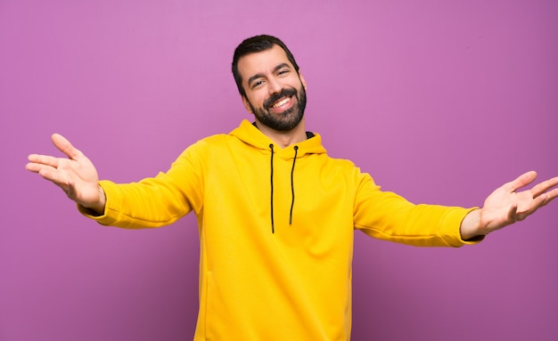 Handsome man with yellow sweatshirt presenting and inviting to come with hand