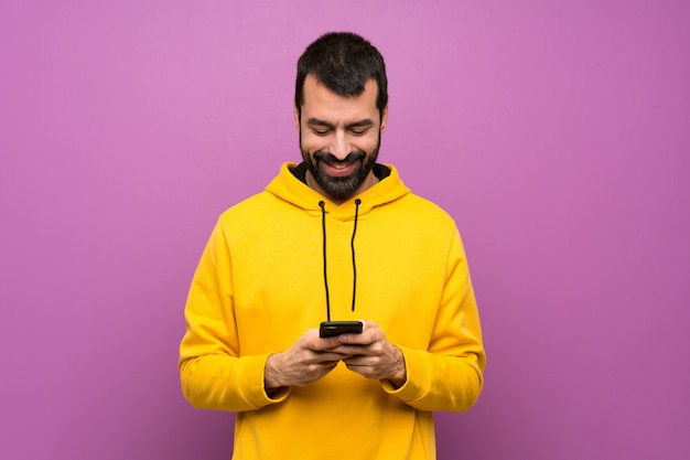 Handsome man with yellow sweatshirt sending a message with the mobile