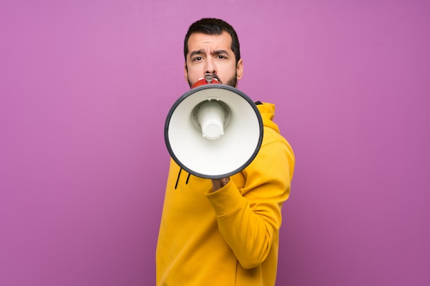 Handsome man with yellow sweatshirt shouting through a megaphone