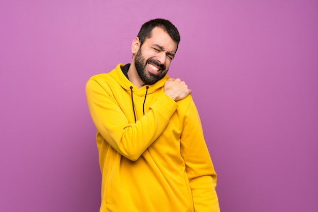 Handsome man with yellow sweatshirt suffering from pain in shoulder for having made an effort