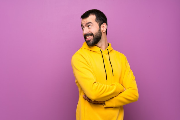Handsome man with yellow sweatshirt with arms crossed and happy