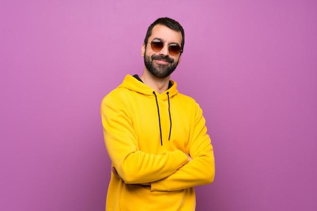 メガネと笑みを浮かべて黄色のスエットシャツを持つハンサムな男