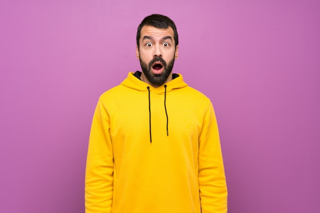 Handsome man with yellow sweatshirt with surprise facial expression
