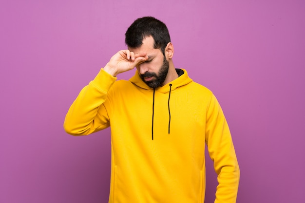 Handsome man with yellow sweatshirt with tired and sick expression
