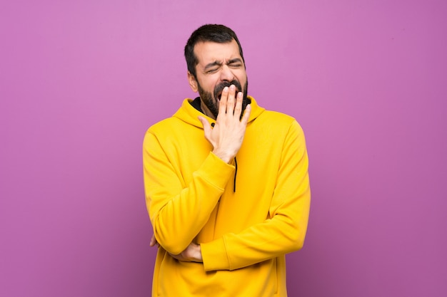 Handsome man with yellow sweatshirt yawning and covering wide open mouth with hand