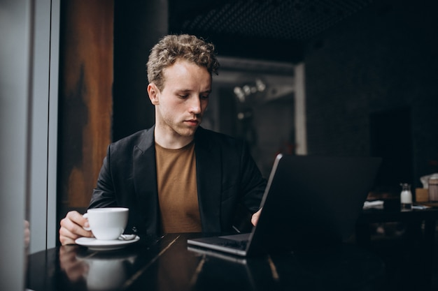 Handsome man working on a computer in a cafe and drinking coffee