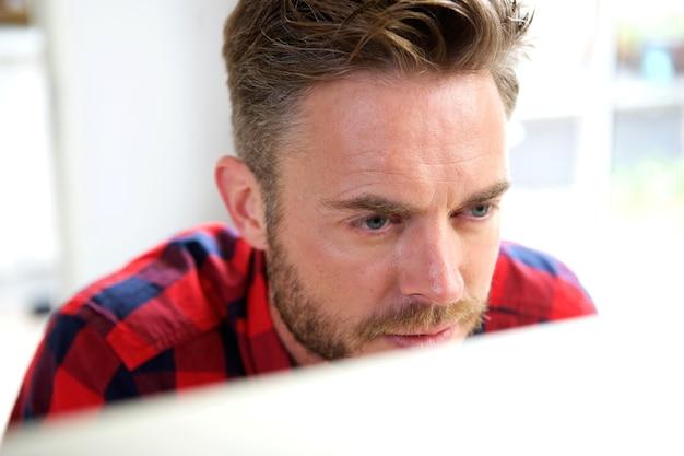 Handsome man working behind computer screen