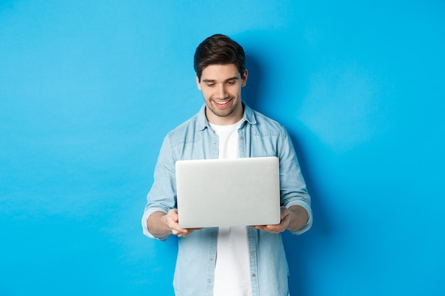 Handsome man working on laptop, smiling and looking at screen satisfied, standing against blue background