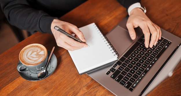 직장에서 노트북에서 일하는 잘 생긴 남자. 커피와 메모장 작업 테이블에서 컴퓨터에 정보를 입력하는 사업
