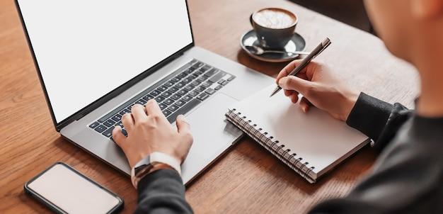 직장에서 노트북에서 일하는 잘 생긴 남자. 커피, 전화 및 메모장 작업 테이블에서 컴퓨터에 정보를 입력하는 사업