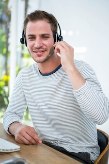 Handsome man working with headset in a bright office