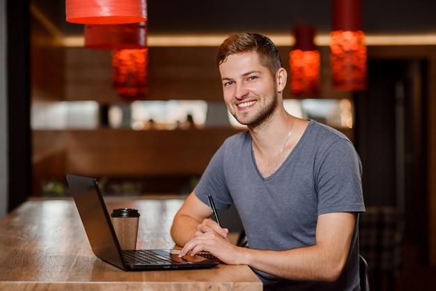 Красивый человек, работающий с ноутбуком в кафе.