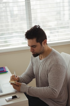 Handsome man writing on sticky note