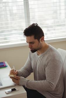 Uomo bello che scrive sulla nota adesiva