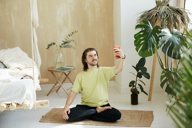 Handsome man in yellow shirt sitting in yoga pose with phone, lovely happy yoga teacher in lotus asana using telephone for online lesson