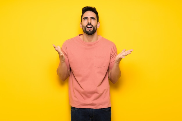 Handsome man over yellow wall frustrated by a bad situation