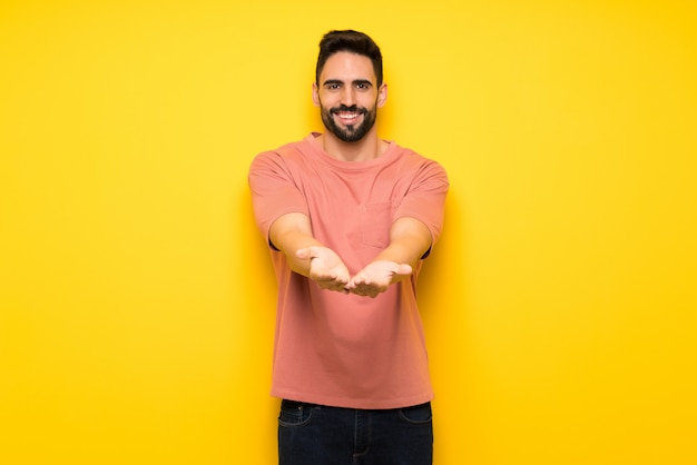Handsome man over yellow wall holding copyspace imaginary on the palm to insert an ad
