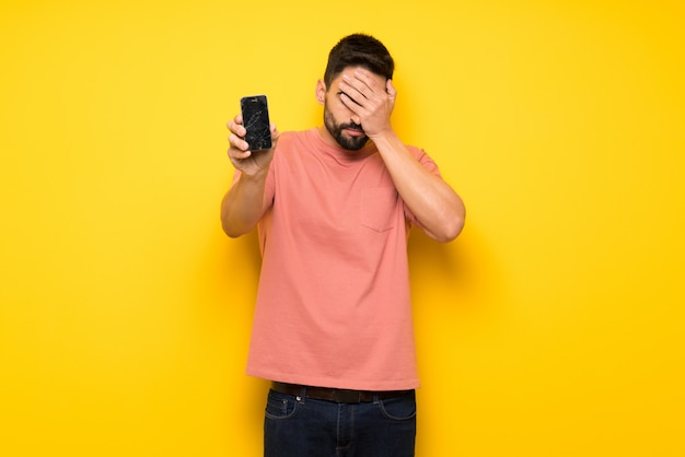 Handsome man on yellow wall with troubled holding broken smartphone