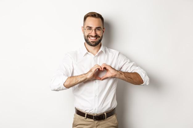 ハンサムな管理ハートサインを表示し、笑顔、私はあなたのジェスチャーを愛し、白い背景の上に立っています。