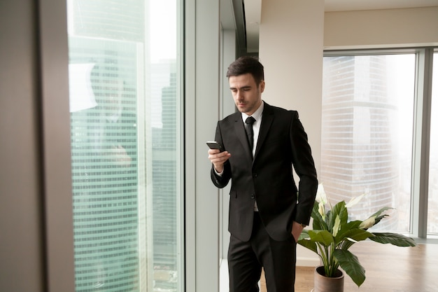 Handsome manager searching contact in smartphone