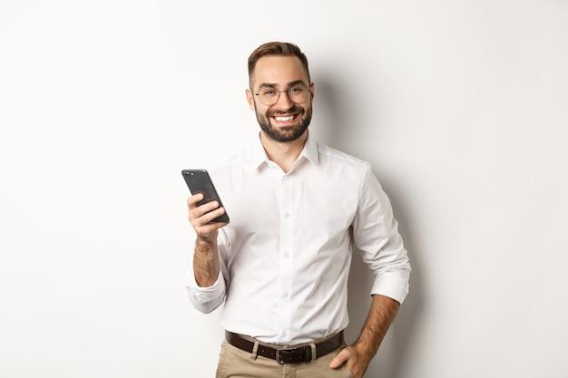 Красивый менеджер с помощью смартфона и довольные улыбки, отправка текстового сообщения, стоя.