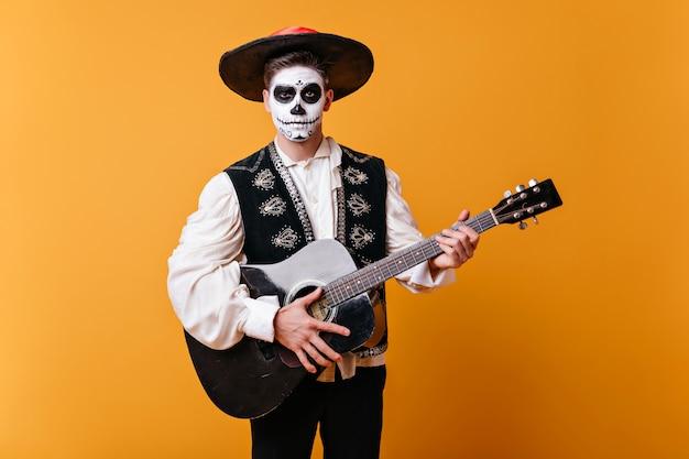 黄色の壁に立っているゾンビ化粧のハンサムなマリアッチ。ハロウィーンでギターを弾くソンブレロのインスピレーションを得た男。