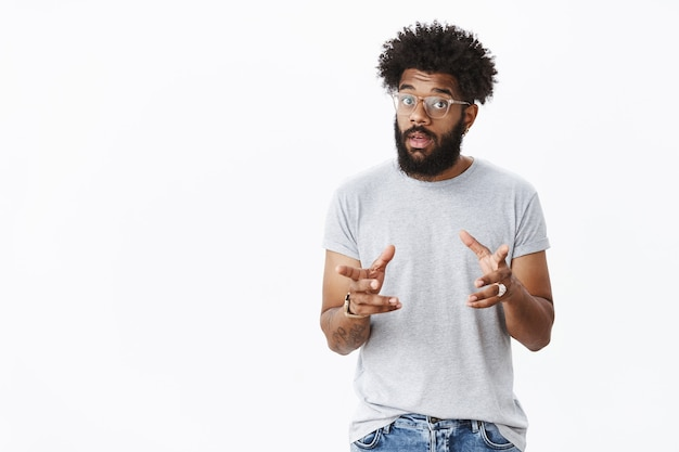 Красивый бородатый мужчина-афроамериканец в очках с татуировками жестикулирует и машет руками, когда разговаривает, объясняя, как работает продукт, поднимая брови, описывая вещь покупателю