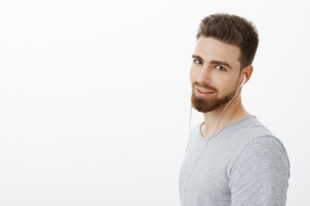 Bel giovane ragazzo caldo maschile e fiducioso con barba e baffi che indossa gli auricolari guardando con bellissimi occhi azzurri audaci e sicuri di sé in posa sul muro bianco