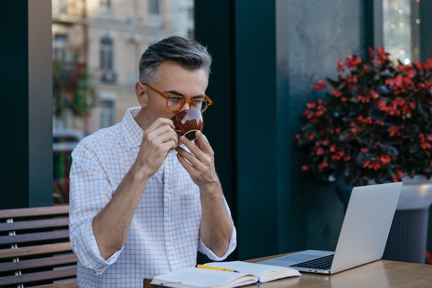 Handsome mature businessman drinking coffee in cafe. coffee break concept