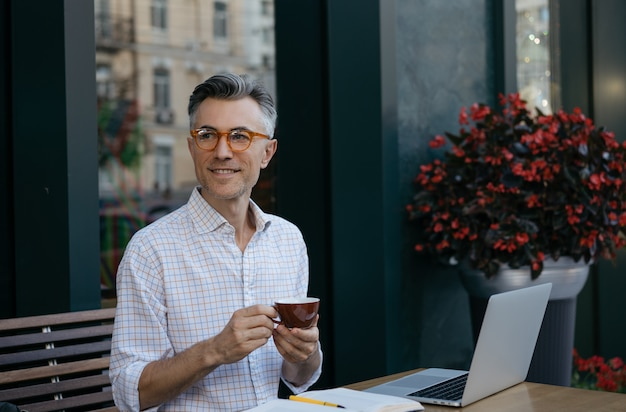 Handsome mature businessman drinking coffee in modern cafe