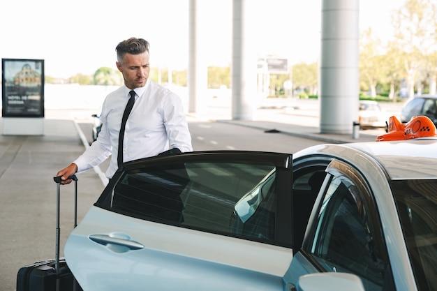 タクシーに入るハンサムな成熟した実業家
