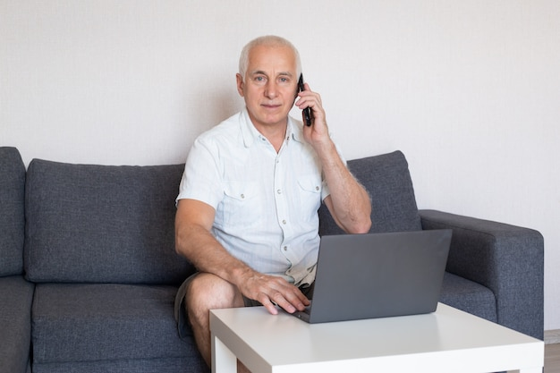 Handsome mature businessman is talking on the mobile phone and smiling while working in home office