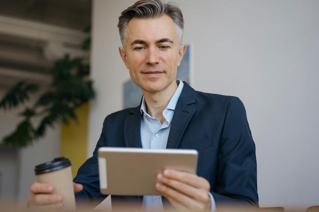 オフィスでデジタルタブレットを使用してハンサムな成熟したビジネスマン。自宅で仕事をしているコーヒーのカップを保持している成功したフリーランサー