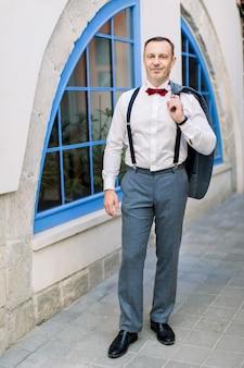 赤い蝶ネクタイとサスペンダーで白いシャツを着たハンサムな成熟した白人男性の新郎は、街の屋外の大きな青い窓のあるヴィンテージの建物の前でポーズをとって、ジャケットを保持します