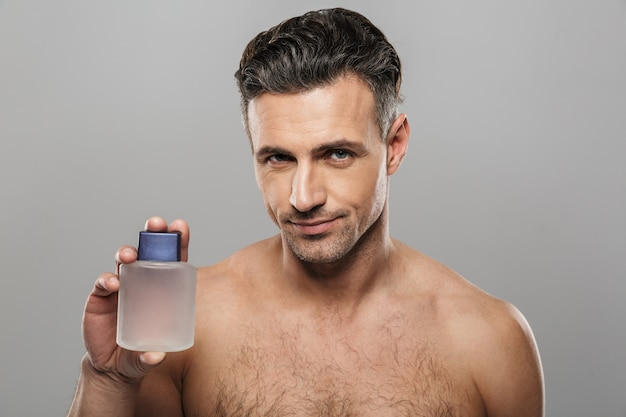Handsome mature cheerful man holding perfume.