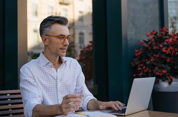 Красивый зрелый разработчик, работающий с ноутбуком и держащий стакан воды
