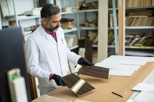 Красивый зрелый инженер в лаборатории осматривает керамическую плитку
