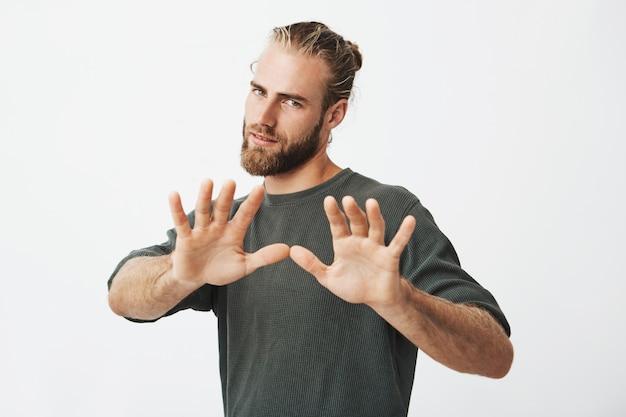 Bel ragazzo maturo con la barba, tenendosi per mano davanti a lui. ferma gesto