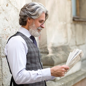Handsome mature male reading newspaper