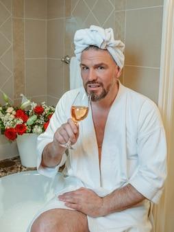 泡とバスルームに座っている彼の頭の上の白いバスローブとタオルでゲイのハンサムな成熟した男