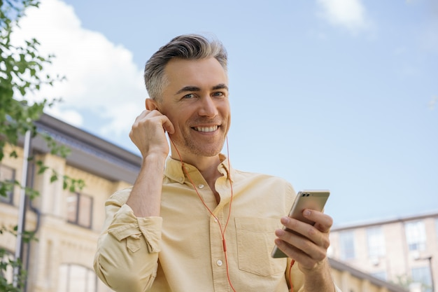 Handsome mature man holding mobile phone, listening to music, looking at camera, smiling