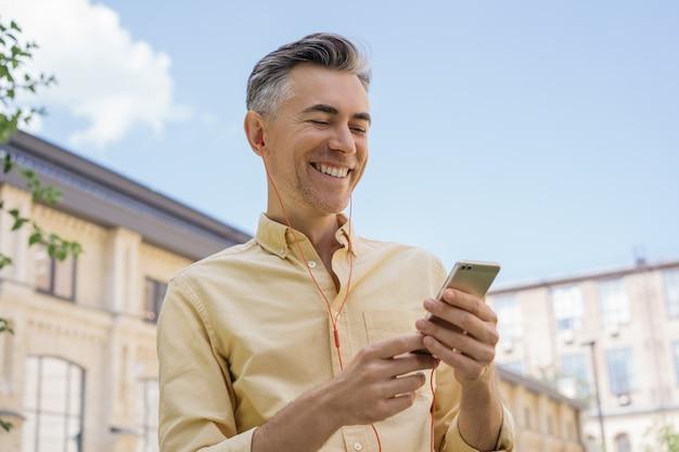 Красивый зрелый мужчина держит мобильный телефон, слушая музыку