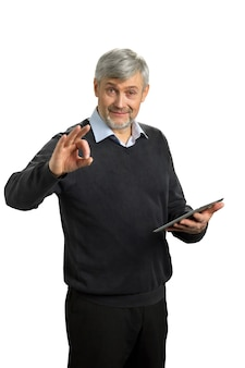 확인 표시를 보여주는 잘 생긴 성숙한 남자. 화이트에 제스처 확인을 보여주는 디지털 태블릿 노인.