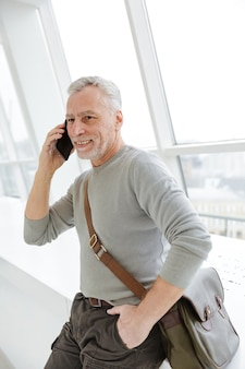 Handsome mature man smiling and talking on cellphone while standing near windows indoors
