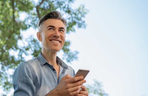 Handsome mature man using mobile phone, shopping online